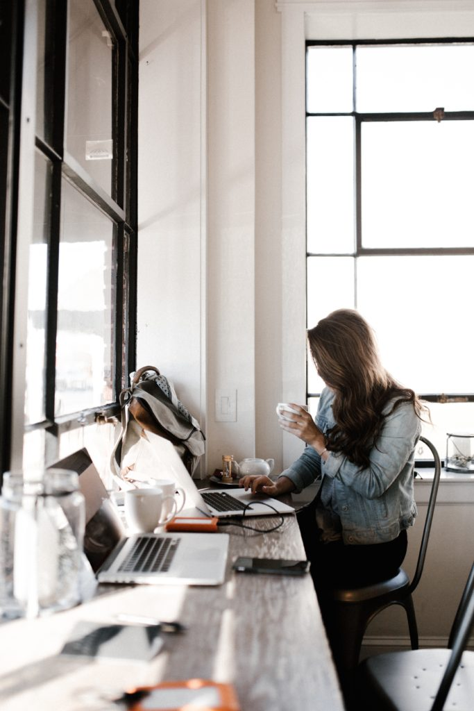 woman entrepreneur sitting at desk with laptop by window