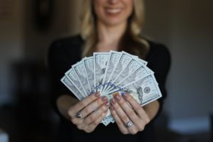 woman with 100 dollar bills earn what you are really worth