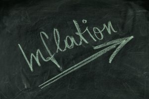 blackboard with the word inflation written on it with upward slanting arrow
